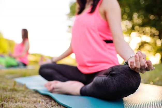 Las chicas hacen yoga o fitness en el césped al aire libre.