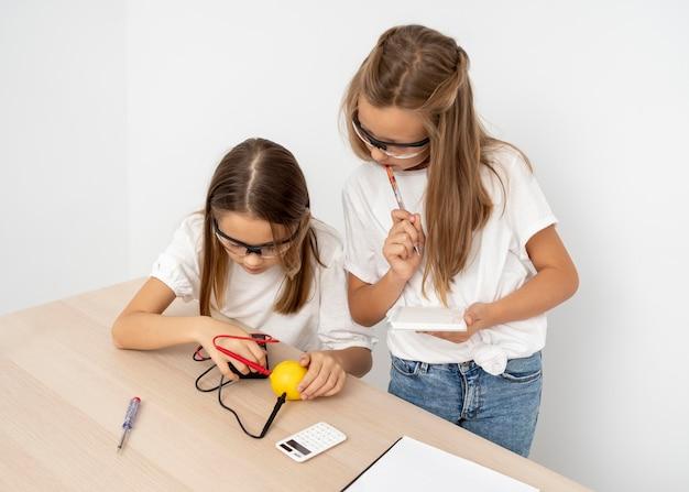 Chicas haciendo experimentos científicos con limón y electricidad.