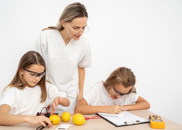 Chicas haciendo experimentos científicos con limones y electricidad.
