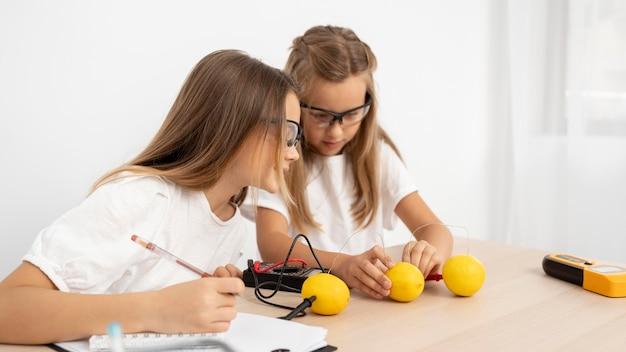 Chicas haciendo experimentos científicos con limones.