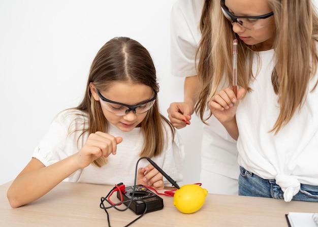 Chicas haciendo experimentos científicos con maestra y limón.