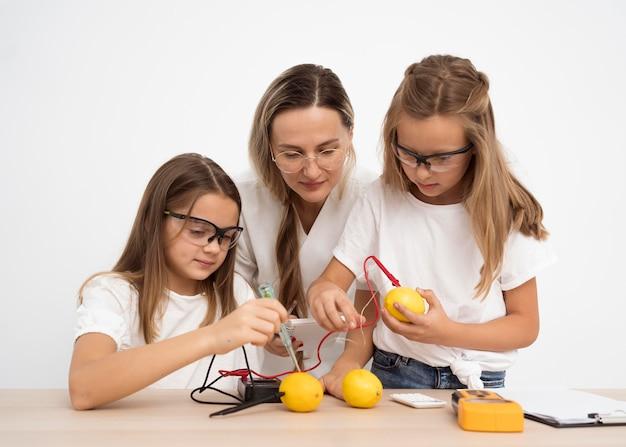 Chicas haciendo experimentos científicos con maestra y limones.