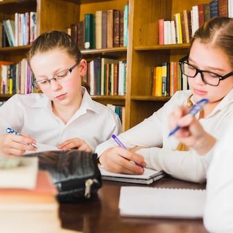 Chicas haciendo la tarea en cuadernos en el escritorio