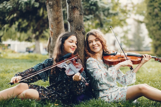 Chicas hermosas y románticas en un parque con un violín