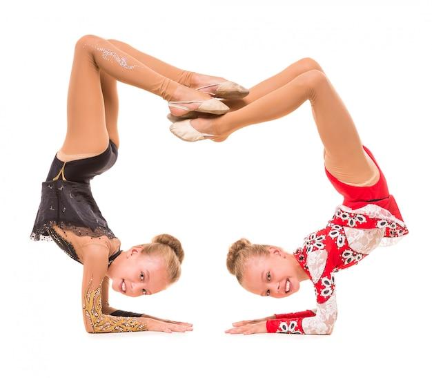 Las chicas con hermosos chándales demuestran los ejercicios.