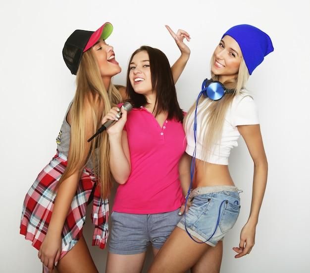 Chicas hipster de belleza con un micrófono cantando y divirtiéndose
