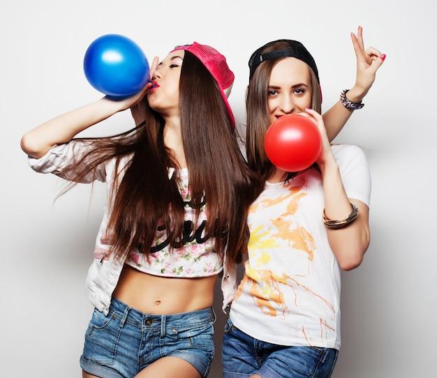 Chicas hipster sonriendo y sosteniendo globos de colores