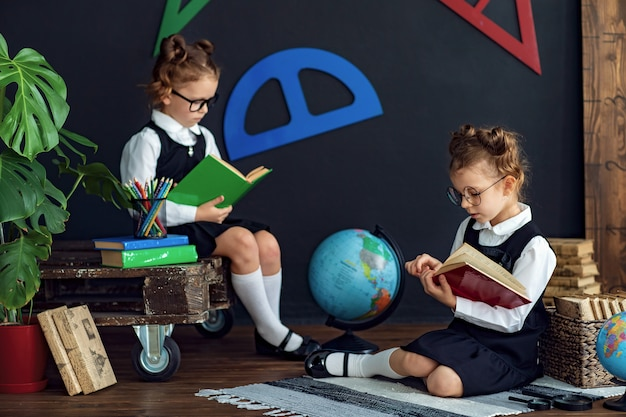 Chicas inteligentes leyendo libros en la escuela