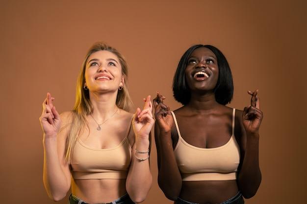 Chicas internacionales sonrientes felices que se encuentran aisladas sobre fondo naranja oscuro