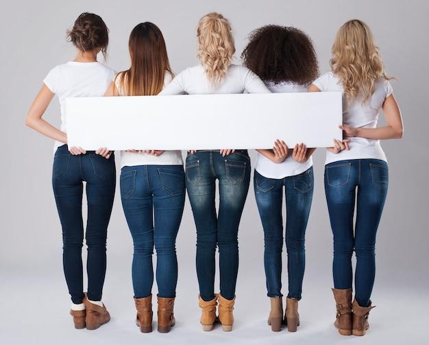 Chicas en jeans sosteniendo pancarta vacía