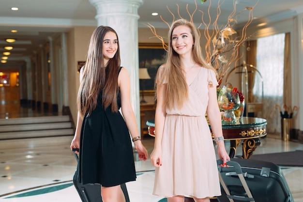 Chicas jóvenes cerca del mostrador de recepción en el hotel. chicas jóvenes vienen al hotel.