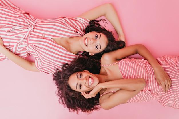 Chicas jóvenes disfrutando de la sesión de fotos. señoras en trajes a rayas riendo.