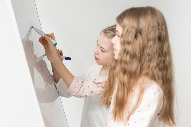 Chicas jóvenes lindas dibujo en pizarra