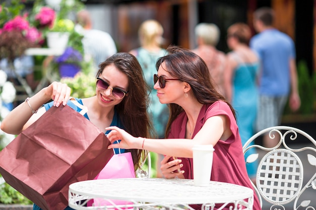Chicas jóvenes de moda con bolsas de compras en el café al aire libre. venta, consumismo y concepto de personas.
