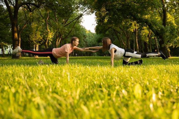 Las chicas jóvenes practican deportes en la naturaleza.
