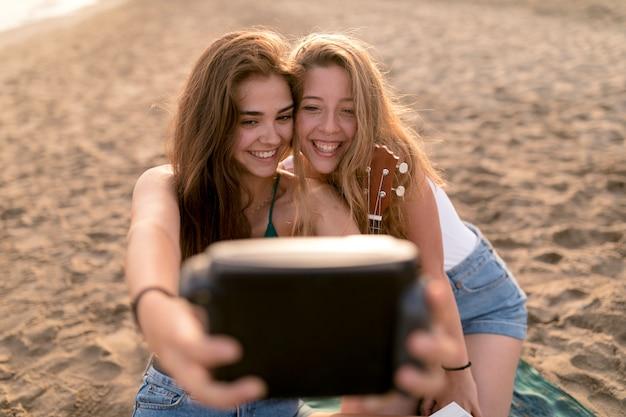 Chicas jóvenes sonrientes que toman el autorretrato de la cámara instantánea en la playa