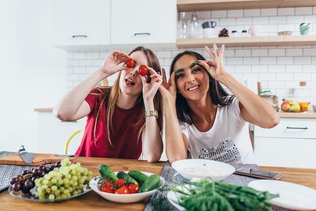 Chicas jugando en la cocina con verduras.