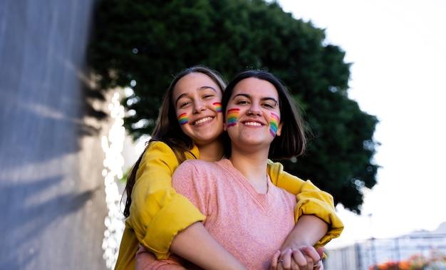 Chicas lesbianas que se divierten pintándose y con la bandera lgtb en el día del orgullo concepto lgtb