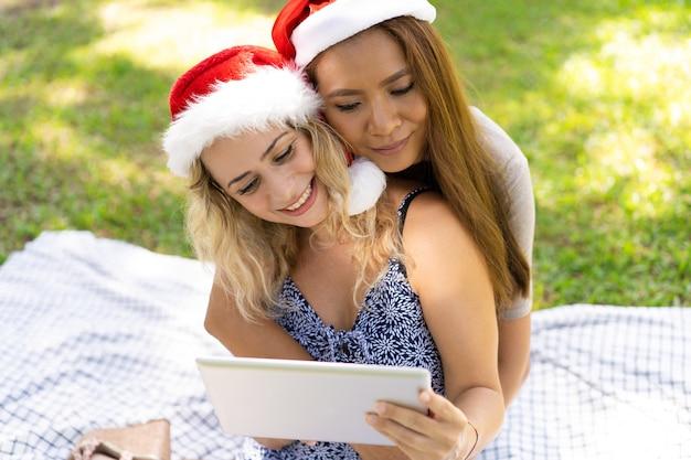 Chicas lesbianas sonrientes abrazándose mientras ven un video en una tableta