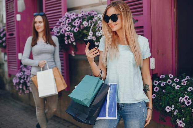 Chicas lindas con bolsa de compras en una ciudad.