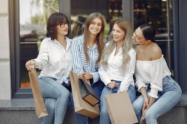 Chicas lindas con bolsa de compras en una ciudad
