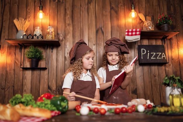 Chicas lindas con delantales y sombreros leyendo el libro de recetas juntas mientras cocinan sabrosa pizza en la acogedora cocina de su casa