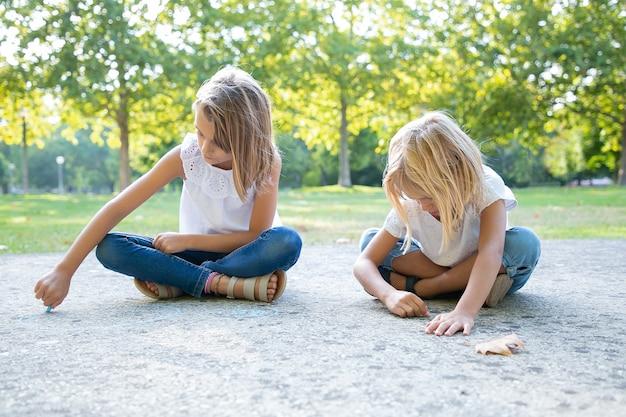 Chicas lindas enfocadas sentadas y dibujando con coloridos trozos de tizas. vista frontal. concepto de infancia y creatividad.