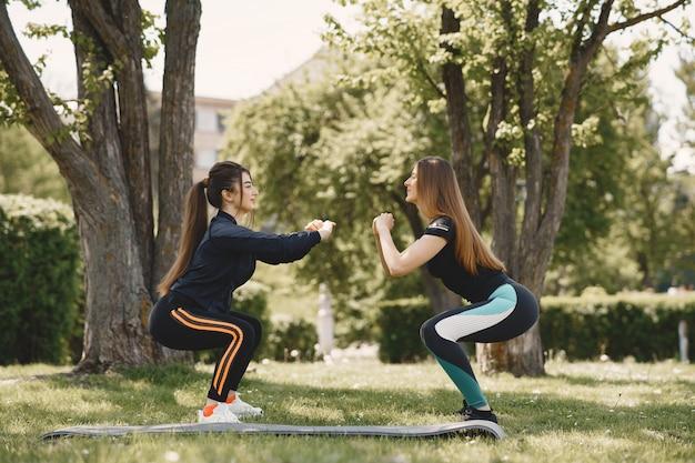 Chicas lindas haciendo yoga en un parque de verano