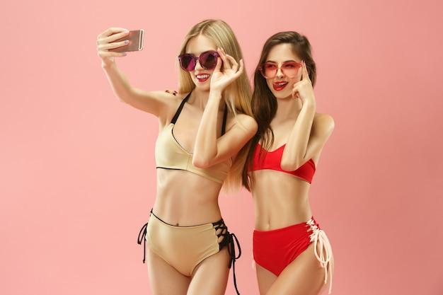 Chicas lindas en traje de baño posando y haciendo foto selfie en teléfono móvil en el estudio.