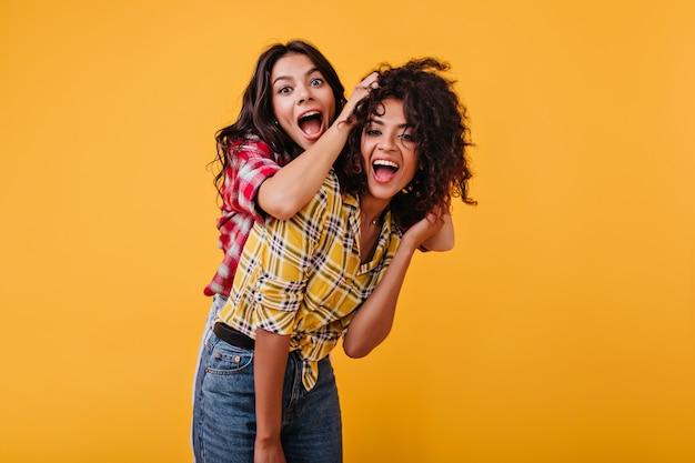 Las chicas locas y emocionales están jugando y divirtiéndose. la mujer se ríe y juega con el pelo de su novia mulata.