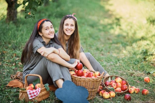 Chicas con manzana en el huerto de manzanas