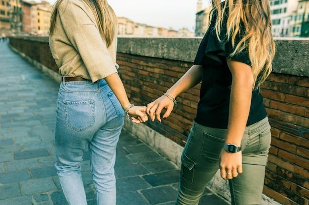 Chicas mejores amigas cogidas de la mano y caminando