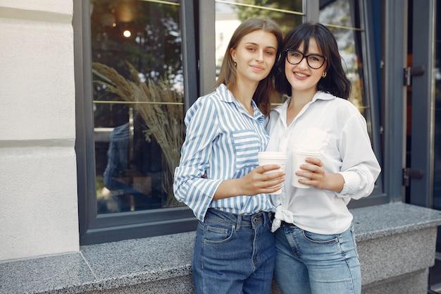 Chicas de moda de pie en la calle