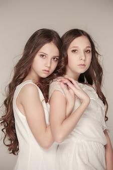 Las chicas de moda de pie juntas y posando