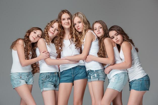 Las chicas de moda de pie juntos y mirando a la cámara sobre fondo gris de estudio