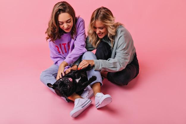 Chicas de moda sentadas en el suelo y jugando con un perrito divertido. señoras entusiastas en ropa casual divirtiéndose con bulldog francés negro.