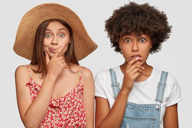 Chicas multiétnicas emocionales estupefactas miran fijamente a la cámara con desconcierto