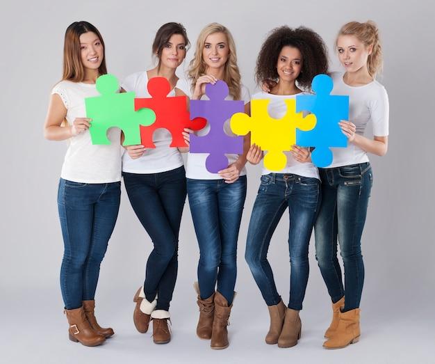 Chicas multiétnicas con rompecabezas de colores