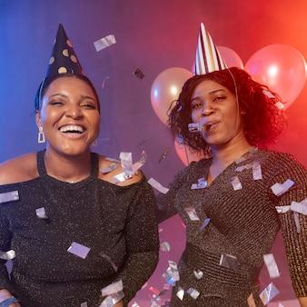 Chicas pasando un buen rato con sombreros de fiesta y confeti.