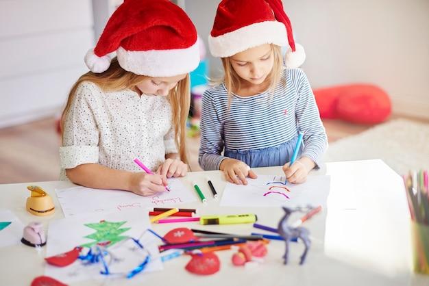 Chicas pensativas dibujando cuadros navideños