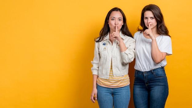 Chicas pidiendo silencio sobre fondo amarillo