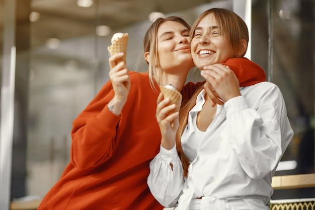 Chicas de pie en una ciudad de verano con helado