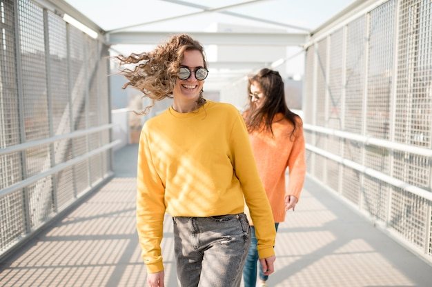 Chicas de pie en un puente en la ciudad
