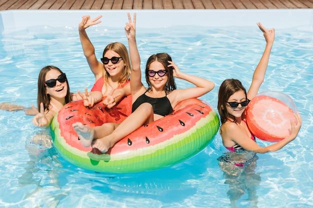 Chicas en la piscina mostrando el signo de paz