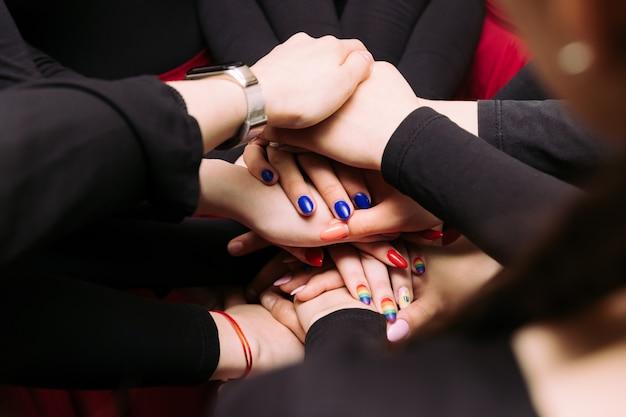 Las chicas se ponen las manos una sobre la otra. la gente junta sus manos. concepto de cooperación de trabajo en equipo de apoyo grupal.