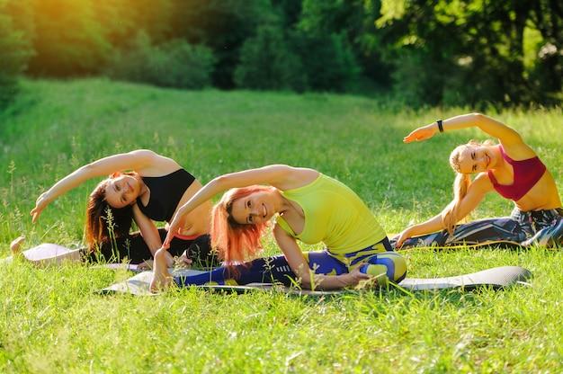 Chicas posando yoga afuera en el bosque por la mañana