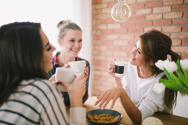 Chicas riendo bebiendo té y hablando
