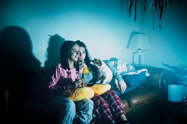 Chicas riendo con perro viendo la televisión