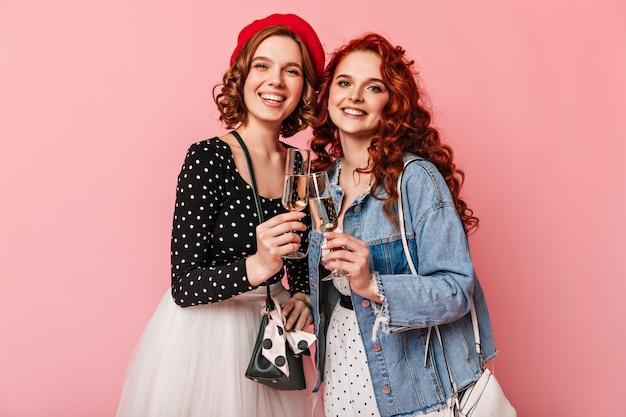 Chicas rizadas tintineando copas de vino y riendo. amigos refinados bebiendo champán sobre fondo rosa.