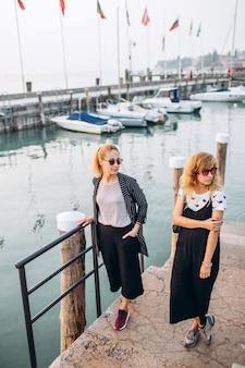 Chicas rubias con gafas de sol chicas caminando por el paseo marítimo del lago de garda, italia.